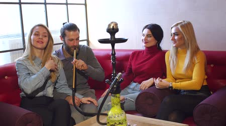 курильщик : A group of cheerful friends resting in a cafe, they smoke hookah, talk and laugh. Modern young people smoke hookah in a modern restaurant on the background of a large window. Slow motion. Стоковые видеозаписи