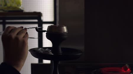 marijuana : Tongs and coal hookah. Close-up glass hookah and man hand holding a coal with tongs. Close-up of a man with forceps changes a burning coal in a hookah in a cafe. Stock Footage