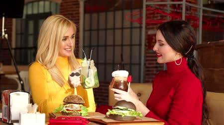 elegant dessert : Two happy girls, a blonde and a brunette, sit in a cafe in bright sweaters eat burgers and talk. Two smiling girls drink cocktails and eat burgers in a bright restaurant
