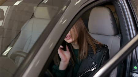 документация : Happy girl talking on the phone while driving a new car in the showroom, she is very emotionally happy to buy a new car. New car as a gift for a young girl.