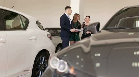 vendedor : A handsome man car salesman is talking to two charming girls in a car dealership among many different cars. Two girls came to the showroom to choose a new car. Vídeos