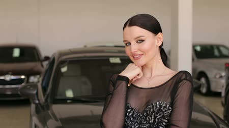 prawo jazdy : Portrait of a gorgeous girl with bright make-up in a black dress with keys to a new car in the showroom. Wideo