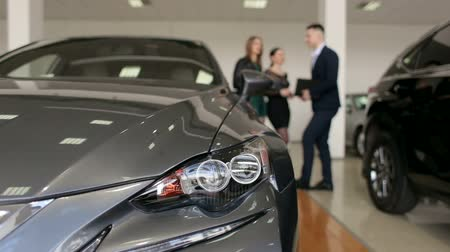representante : The image of the car in the showroom, in the background a man the seller advises two young girls when choosing a new car. Blurred background. Silhouette of people in the showroom.