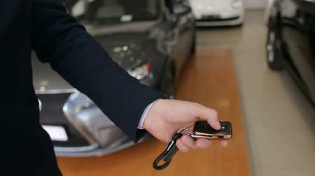 bérlet : Close-up of a man presses a button on the remote car alarm, he opens or closes the car door. Mens hand presses on the remote control car alarm systems. Stock mozgókép