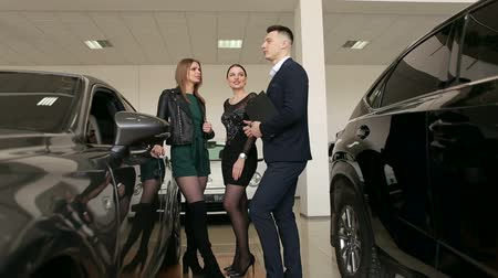képviselő : Two gorgeous girls talking to a sales consultant in a car dealership, they want to buy a new car. The process of working in the showroom.