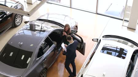 grande quantidade : Top view on the auto shop with lots of cars. The car dealer gives the young happy girl the keys to her new car. Buying a new car. Stock Footage