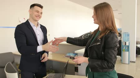latino americana : A young car salesman gives the young girl the keys to the new car and they shake hands after a successful purchase. Successful purchase or rental of a car in a modern auto show.