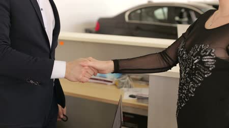 трейдер : Close-up of a car salesman shaking hands with a young elegant girl and giving her the keys to her new car in a modern auto show.