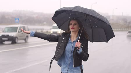 raincoat : Beautiful girl on the road in heavy rain under an umbrella trying to catch a car. Hitchhiking.