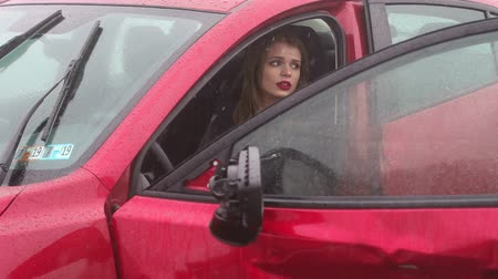 engedély : Close-up of a frightened girl sitting in the car after an accident in the rain, she holds her head and cries. Slow motion. Car accident on the road. Stock mozgókép