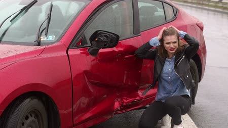 istek : A frightened girl is sitting next to her broken car after a strong car accident in the rain on the track, she has stress and severe pain. Car accident. Slow motion. Stok Video