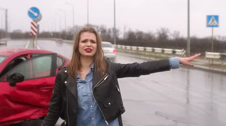 ignore : Frightened girl crying on the road after a strong car accident in the rain, she tries to stop the passing cars, but all pass by. People ignore a car accident on the road. Stock Footage
