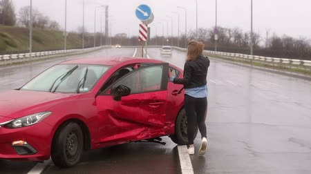 elpusztított : A young girl stands near a broken car on the road in the rain, she is frightened and wounded. Empty road. The girl after a car accident on an empty wet road does not know what to do. Stock mozgókép