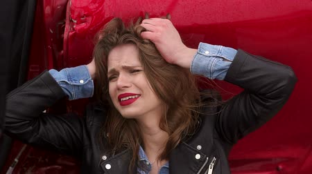 preocupado : Close-up of a girl crying sitting on the ground near a broken car, she was in an accident in bad weather on the road. The girl is hurt and scared. Slow motion. Steam from the mouth. Stock Footage