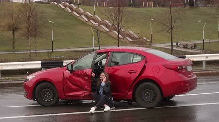 členění : The upset girl sits on the earth near the broken car, other car crashed into her and left. The girl calls on the phone and asks for help, she cries. Car accident in the rain.