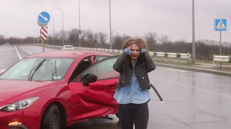 prawo jazdy : A frightened young girl got into a car accident on a wet road after the rain, she is injured and scared. The girl stands near the broken car in the rain on an empty road and cries. Slow motion.