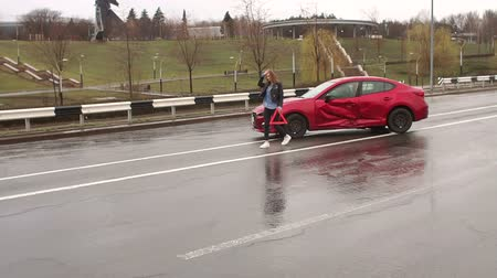 reflektör : A young girl in jeans and a leather jacket sets an emergency stop sign near her wrecked car in rainy weather. Car accident on the road, the girl puts a warning sign near the car. Stok Video