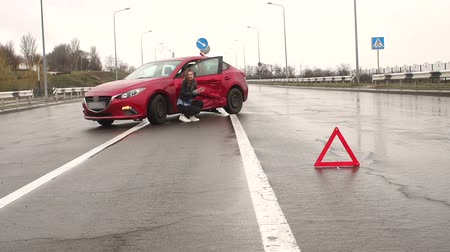 členění : Young scared girl standing on the road near the broken car, she was in a car accident and waiting for help. Next to the car is a warning sign of an emergency stop.