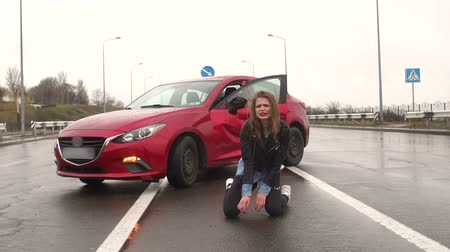 celkový : Teen girl sitting on the wet asphalt on the road near the wrecked car, an accident occurred on the road. An injured, frightened girl sits on the ground after an accident and cries. Slow motion.