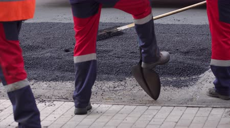 roadwork : Workers on a road construction, industry and teamwork. Fresh asphalt construction. Bad road. Roller and workers on asphalting and repair of city streets. Close-up. High resolution.