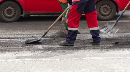 being removed : Workers removed the old cut asphalt in the tractor and truck shovels. Repair work on the road. New asphalt. A road worker collects fresh asphalt with a panicle on the part of the road being repaired.