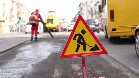 city limits : Roadworks signs on a street. Roadworks sign on a road. Road sign repair work and detour arrow. Repair work on the road. Workers laid new asphalt.