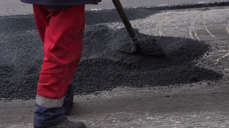 мощение : Workers scatter asphalt with shovels at road construction. Worker lays asphalt on a road repair road paving.Road construction crew used shovels to scatter more asphalt over the top of the new pavement