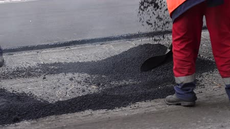 Łopata : Worker man lays asphalt on a road repair road paving. Road construction crew used shovels to scatter more asphalt over the top of the new pavement. At road construction site.
