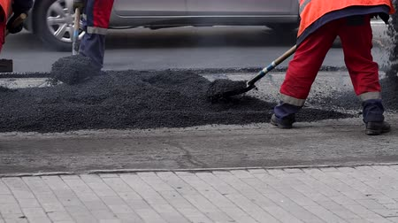 мощение : Worker leveling fresh asphalt on a road construction site, industrial buildings and teamwork. Стоковые видеозаписи