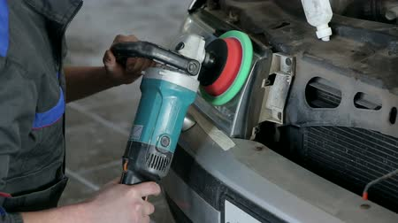 tampon : Close-up of a mechanic polishes the headlight with a grinding machine. Repair and care of the car at the service station.