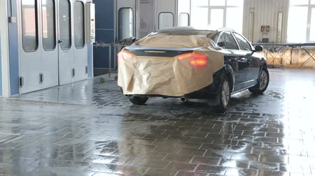 repaint : The machine is covered with protective paper drives into the painting unit for painting the rear hood. Painting the car body at the service station. Stock Footage