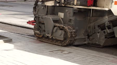crawler : Road works. Dismantling of asphalt pavement. A fragment of a trimming unit-track. A large industrial tractor cuts off the old asphalt. Slow motion.