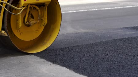 crawler : Close-up of an asphalt rink lays new asphalt on the road. Repair of roads. The repair work of industrial machines in the city.