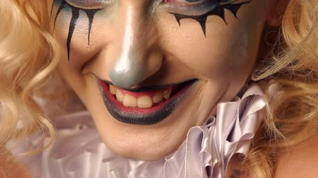 vampiro : Close-up portrait of an excited blonde woman with make-up in halloween. Eerie makeup on the face of a girl with black streaks and black lips. Fashionable makeup for Halloween party, horror and mystery Stock Footage