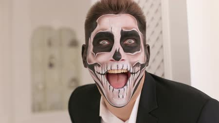oldalt : Close-up portrait of a man with a skull makeup dressed in a tail-coat. Dia de los muertos. Day of The Dead. Halloween. Portrait of man in suit with Halloween skull make-up showing his emotions.