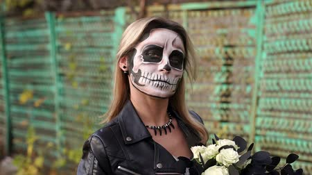 маска : Close-up portrait of a gothic girl in a wedding dress and a creepy make-up. Painted skull on the girls face. Gothic look. Outfit for halloween. Slow motion.