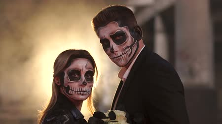 fire suit : Couple with dark skull makeup on the background of burning fire and smoke. Silhouette. Halloween face art. Halloween concept. Zombie. Silhouette. Slow motion