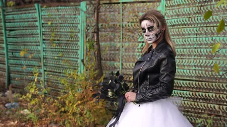 косплей : A creepy bride with a bouquet of black flowers and make-up in the form of a skull stands against a rusty green fence. Woman dressed in costume cosplay horror dead bride or ghost on Halloween festival.