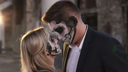 muertos : Couple with dark skull makeup against the background of an abandoned building with columns. Terrible place. Abandoned city. Halloween loving couple in costumes of skeletons and sugar skull make-up. Stock Footage