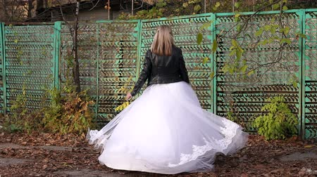 маска : A girl in a wedding dress with a terrible make-up on her face spinning in the autumn against the background of an old abandoned fence. The celebration of Halloween. Halloween or horror concept.