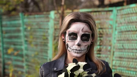 boszorkány : Portrait of a scary girl with make-up on a halloween in the form of a skull with a bouquet of black flowers. Slow motion. Woman in dress and makeup for halloween in the forest. Stock mozgókép