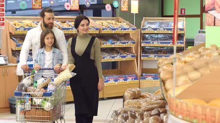 supermarket shelf : Beautiful young parents and their cute little daughter are smiling while choosing baking in the supermarket. Happy family with little girl picking bread from shelf in food store. Stock Footage