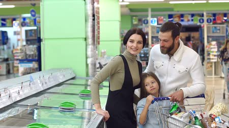 chladič : A young family with a child in the supermarket choose frozen foods. Portrait of a happy smiling family with a daughter near a large refrigerator in the supermarket. Slow motion.