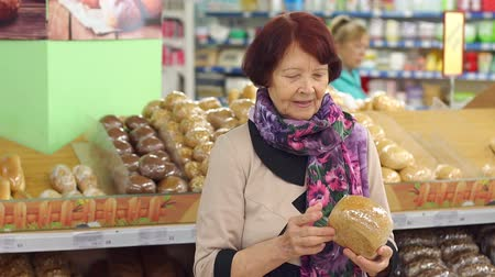 bagietka : Portrait of a cute retired woman in a grocery store in the bread Department. Grandma buys fresh bread at the supermarket.