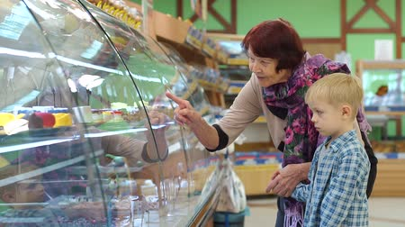 parentes : An old grandmother with a small grandson in the supermarket choose sweets on the counter. Portrait of an elderly woman with a child in the supermarket. A grandmother with a grandson to buy a cake.