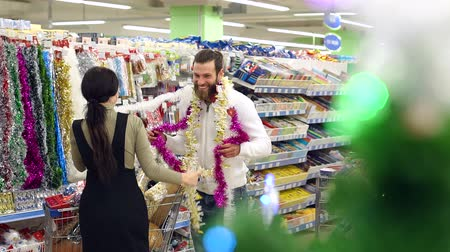 festoon : Happy loving couple buying Christmas decorations and gifts for Christmas. The couple is having fun at the Christmas holidays in the supermarket. Slow motion. Stock Footage