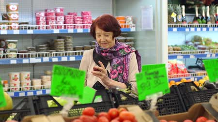 упакованный : An elderly woman with wrinkles on her face chooses and buys products in the supermarket. Slow motion. Cute grandmother buys vegetables in the grocery store.