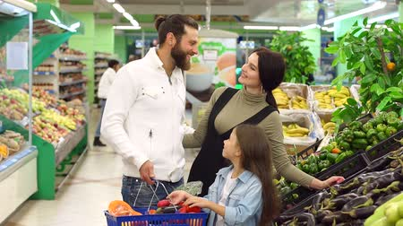 beringela : Happy young parents make purchases with their daughter, they choose fresh vegetables and put them in the basket. Bearded man holding a grocery basket in the supermarket.