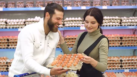 korting : Young happy couple choose eggs in supermarket. Young family buying eggs at the grocery store. Slow motion. Portrait. Stockvideo