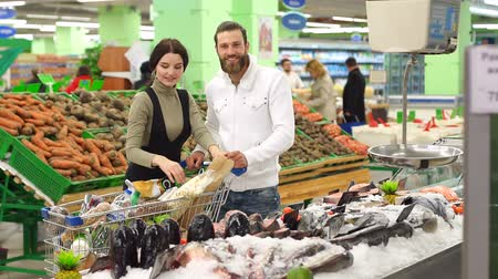 rákfélék : Beautiful young couple is choosing fish and smiling while doing shopping at the supermarket. Couple buying fish. Couple is choosing frozen seafood for dinner in the supermarket.